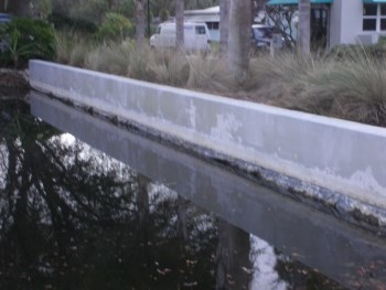Before Repainting of a pond retaining wall in Edgewater, FL